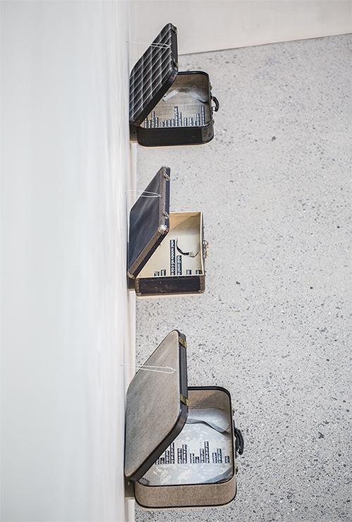 """Das Foto zeigt einen Teil der Ausstellung """"Marienheim"""" der Künstlerin Grid Marrisonie im vorarlberg museum. Drei alte Koffer sind an der Wand montiert. Die Deckel sind aufgeklappt. In den Koffern sind Texte."""