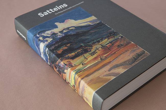 """Foto der Publikation """"Satteins"""" auf altrosafarbenem Hintergrund. Auf dem Schutzumschlag ist ein Gemälde des Künstlers Martin Häusle."""